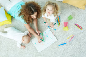 mom with her kids doing art while lying on the floor